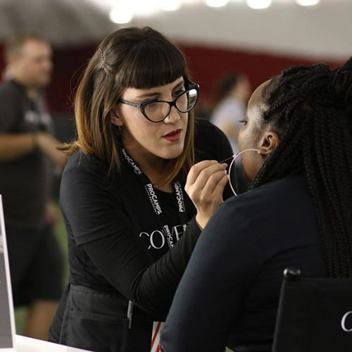 • A CoverGirl makeup artist applying Melting Pout liquid lipstick on a camp attendee