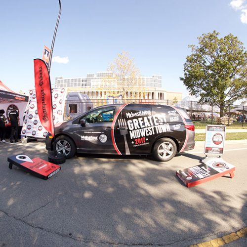 The Midwest Living wrapped vehicle, corn hole board games, tent and photo backdrop at Grange Grove outside Memorial stadium