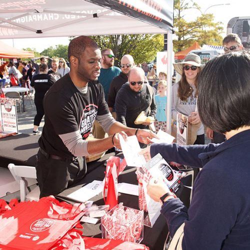 Midwest Living brand ambassador handing out food vouchers and produce bags to guests